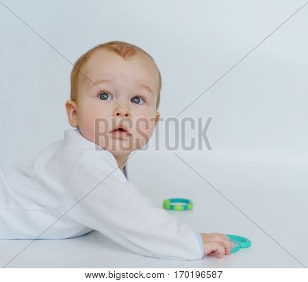 baby child lying on belly weared with teether in mouth