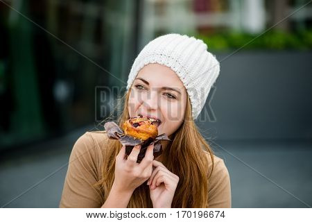 Young woman - teenager in cap eating muffin outdoor in street