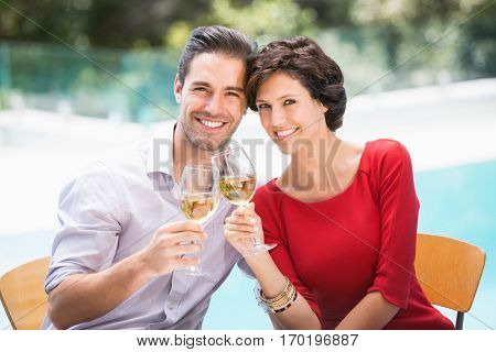 Portrait of smiling couple toasting white wine while sitting at poolside