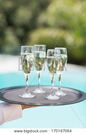 Cropped hands of waiter holding champagne flutes tray at poolside
