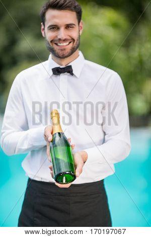 Portrait of smiling waiter holding champagne bottle at poolside
