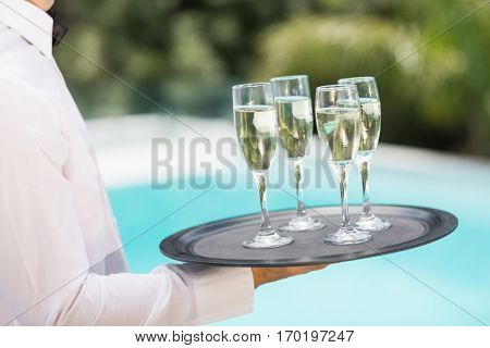 Midsection of waiter carrying champagne flutes on tray at poolside