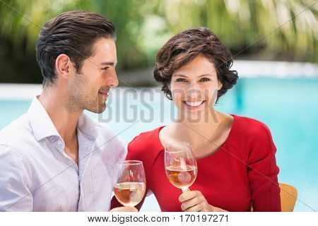 Smiling couple holding white wine while sitting at poolside