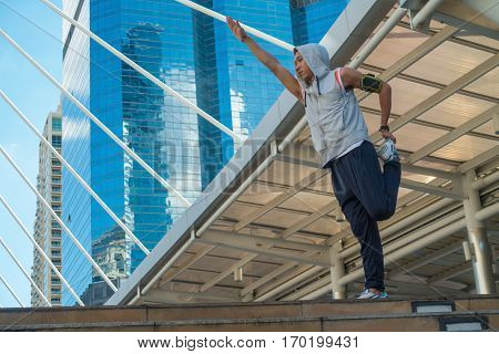 Young Asian sport man warm up by stretching leg before running in city background.