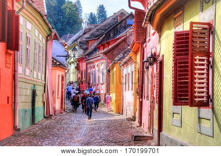 Tourists walking inside the famous citadel of Sighisoara in a summer holiday, Transylvania - Romania