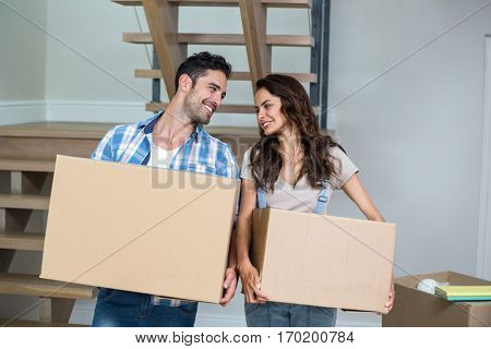 Cheerful couple with cardboard boxes at home