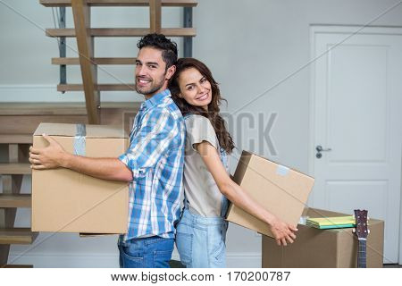 Portrait of cheerful couple with boxes