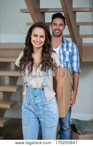 Portrait of cheerful couple carrying cardboard boxes at home