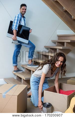 Portrait of smiling man holding computer with woman unpacking objects in new house