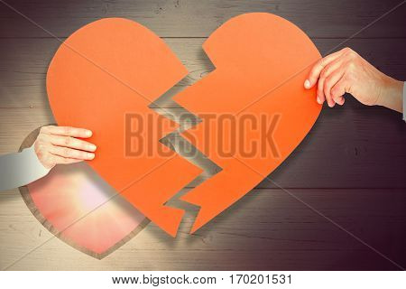 Couple holding broken heart shape paper against heart in wood