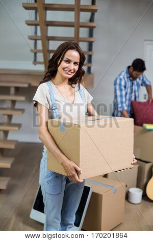 Portrait of smiling woman holding box while standing in new house
