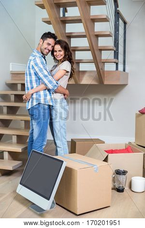 Portrait of cheerful couple hugging while standing at home