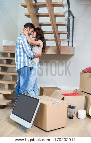 Side view of romantic couple hugging while standing at home