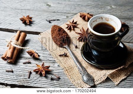 Fragrant spices, coffee in vintage silver spoon and black cup, cinnamon, cloves and anise on sackcloth on rustic wooden table