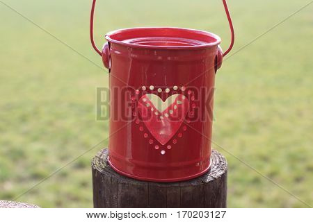 Small red metal bucket with round perforations in the form of a heart, in bucket standing a transparent empty glass, on brown wooden posts, in the background green meadow, In the sun in February 2017 in Häselingen
