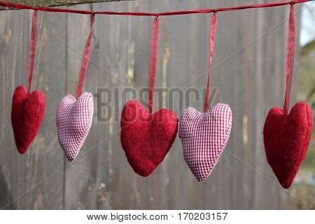 3 fire hearts and 2 checkered cloth heart hanging on the dark red silk thread in the sunshine of Häselingen in February 2017, In the background a brown weathered wooden wall