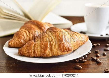 Breakfast scene with fresh croissants, coffee cup, coffee beans and open book. Relaxation morning scene with hot coffee.