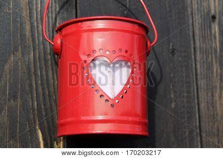 Small red metal bucket filled with round perforations in the form of a heart filled with pink sisal wooden heart, hanging on a brown-gray weathered wooden wall in the background In the sun in February 2017 in Häselingen