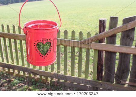 Small red metal bucket with transparent glass with moos and round perforations in the form of a heart, hanging in the wind, in the background, tree, gray - brown- green  weathered garden fence and green meadow, In the sun in February 2017 in Häselingen