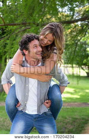 Husband giving a piggy-back to his wife in park