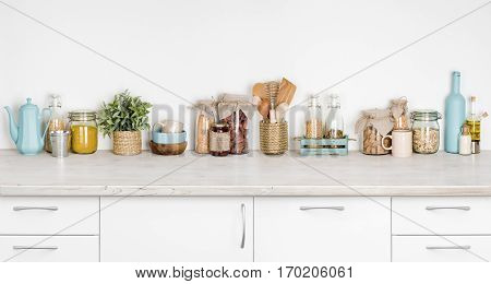 Kitchen bench interior with various herbs spices utensils on white