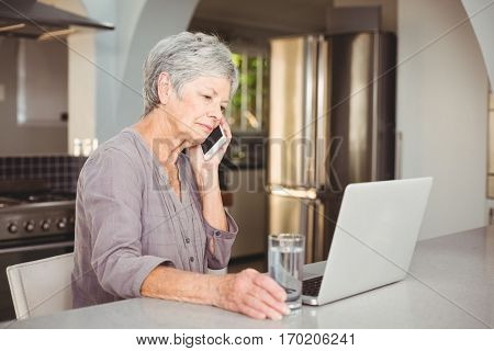 Serious senior woman talking on mobile phone while sitting in kitchen