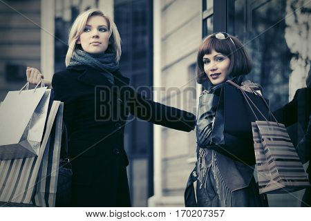 Two young women with shopping bags next to mall door Stylish fashion model outdoor
