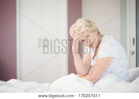 Portrait of senior woman suffering from headache at home