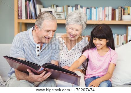 Grandparents showing album to granddaughter at home