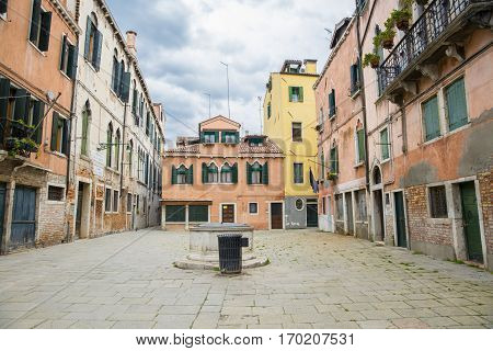 view on a Venetian square or piazza with traditional historic buildings and a well