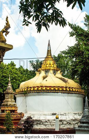 Temple with lots of gold ornamentation and power pole right in front it In Vientiane, Laos