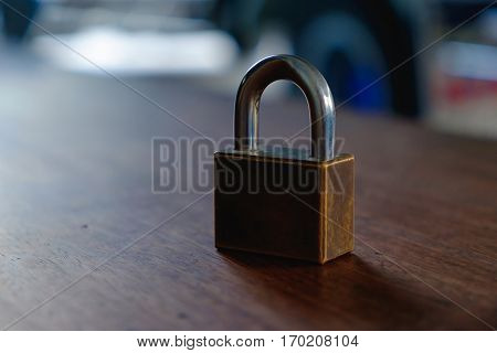 Padlock On The Brown Wooden Table Background.