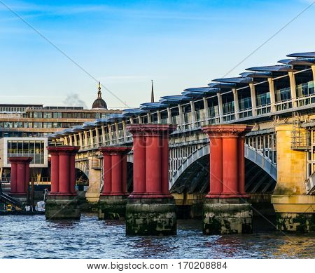red columns in the water against the background of a bridge in London color architecture