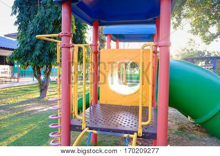 empty playground has colorful slide tube and stair.