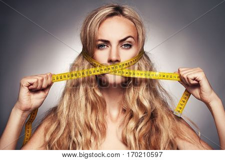 Female covering her mouth measurement tape. Woman on a diet
