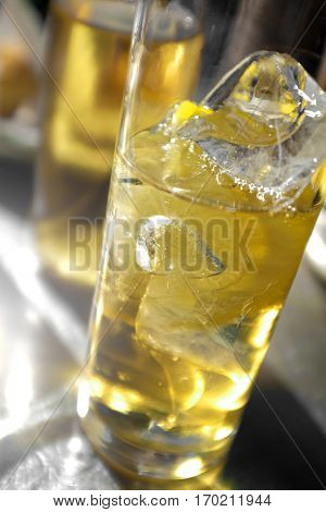 View of a glass with drink and lemon slice with light from behind