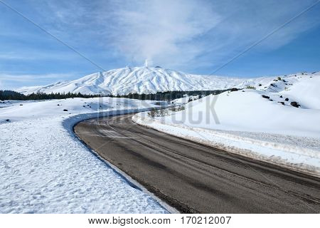 curve road and snow covered Etna Mount, Sicily