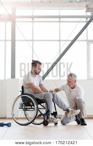 Stretching the leg. Professional involved aged physical therapist helping the disabled man and providing a rehabilitation session while expressing concentration