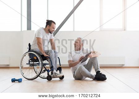 Positive atmosphere. Pleasant friendly aged orthopedist communicating with disabled man and sitting in the gym while expressing positivity and holding the tablet