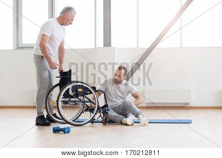 Helping my patient. Proficient caring aged orthopedist helping the disabled man and providing a rehabilitation session while expressing concentration and standing near the wheelchair