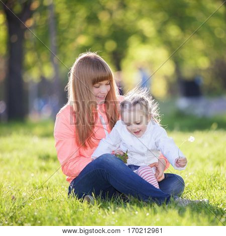 Mother and daughter in the park. Beauty nature scene with colorful background at spring season. Family outdoor lifestyle. Happy woman and cute girl relax on green grass