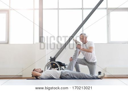 Enjoying the healthy lifestyle . Athletic masterful aged physical therapist helping the disabled man and providing a rehabilitation session while holding the leg of the patient