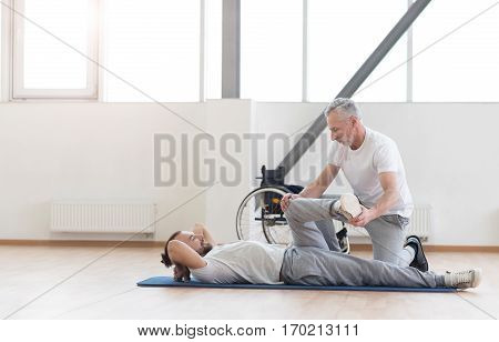 Providing the healthy lifestyle . Confident masterful aged coach helping the disabled man and providing a rehabilitation session while expressing positivity and holding the leg of the patient