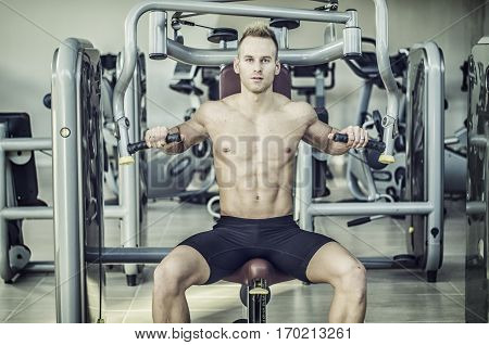 Muscular, shirtless young man in gym exercising pecs on pectoral machine