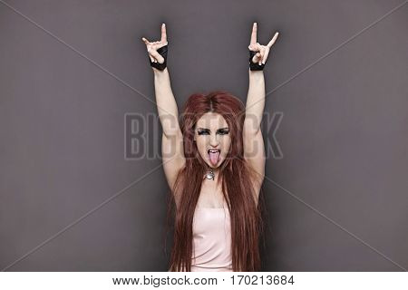 Portrait of funky young woman sticking out tongue and making rebellious gestures over black background