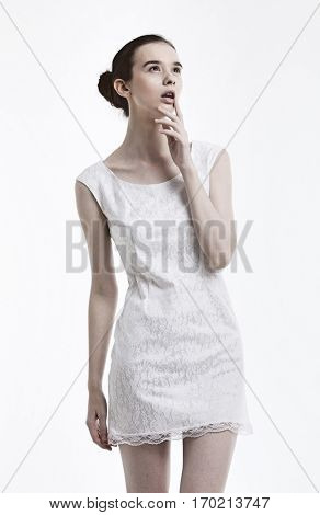 Young woman in dress daydreaming over white background