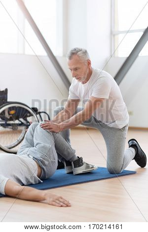 Training the lower body. Experienced positive aged physical therapist stretching the handicapped and providing a rehabilitation session while holding legs of the patient
