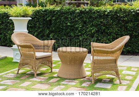 Wicker patio chairs and table in garden