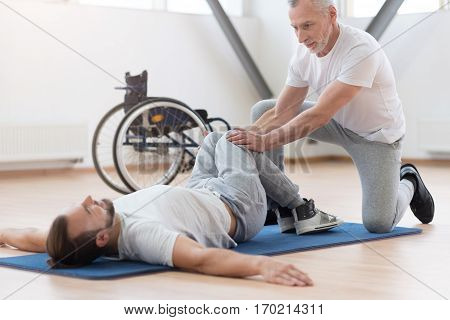 Working out the lower body. Attentive pleasant aged general practitioner stretching the handicapped and providing a rehabilitation session while holding legs of the patient