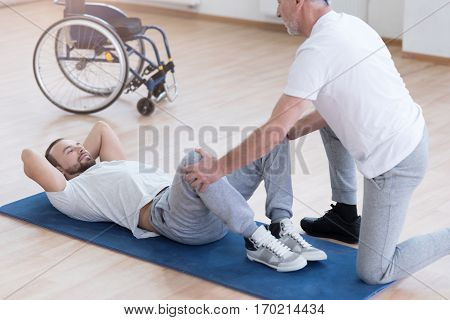 Working out together. Helpful masterful aged general practitioner stretching the handicapped and providing a rehabilitation session while holding legs of the patient